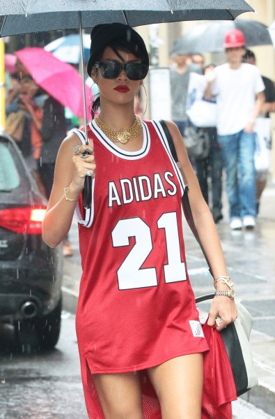 Rihanna shows off her flair with a long back bright red Adidas tee and some Nike sneakers