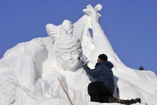 A worker shapes a snow sculpture prior to the Harbin International Ice and Snow Festival in Harbin