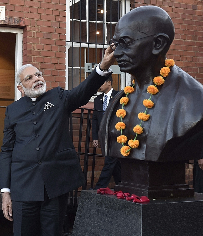 Johannesburg: Prime Minister Narendra Modi touches the bust of Mahatma Gandhi during his visit to Constitutional Hill in Johannesburg on Friday. PTI Photo by Kamal Singh(PTI7_8_2016_000315B)